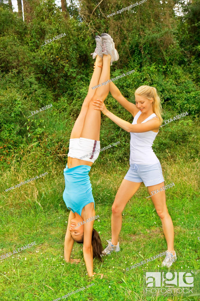 Stock Photo: Two women dressed in sporty clothes working out outdoors and helping each other to complete a handstand.