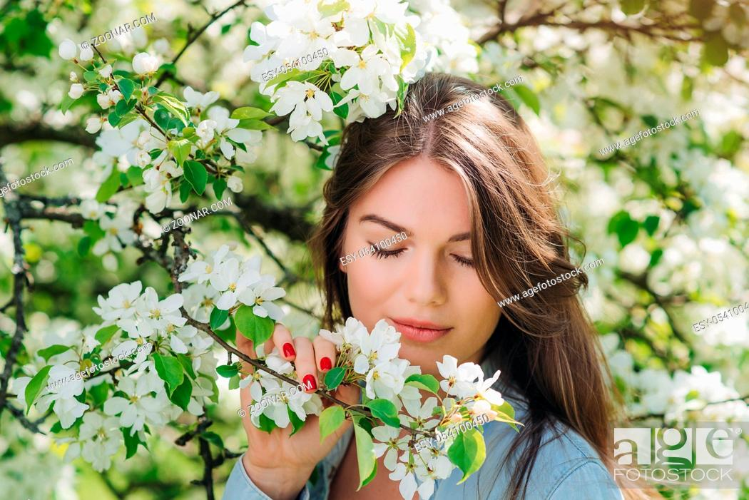 Stock Photo: Beautiful young brunette woman standing near blooming apple tree.