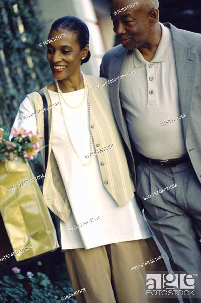 Stock Photo: Mature couple walking with shopping bags.