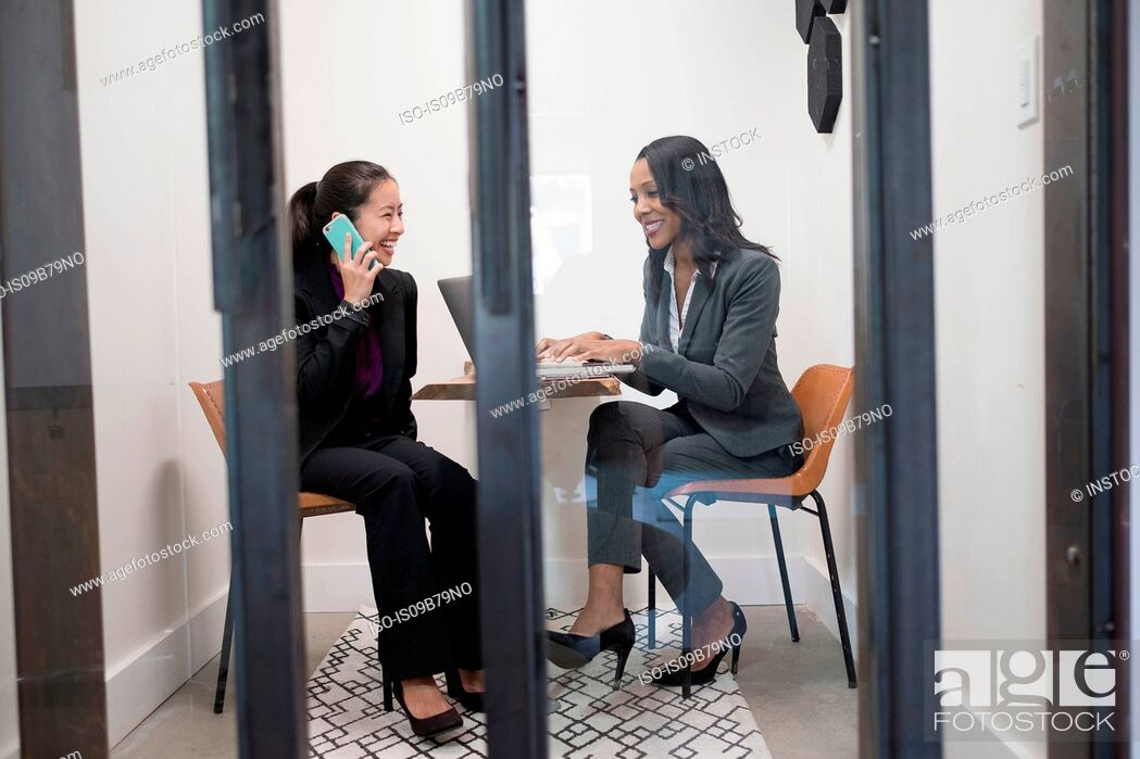 Stock Photo: Two businesswomen in office, using laptop, talking on smartphone.