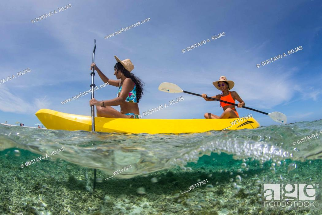 Photo de stock: Two Beautiful Women on Kayak paddling on blue water sea. Travel and Vacation on The Beach .
