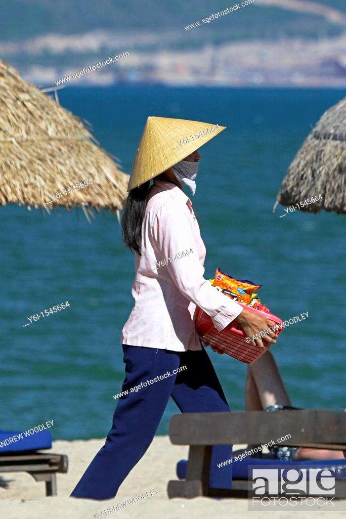 Stock Photo: Woman beach vendor in conical hat walks between woven beach umbrellas Nha Trang south east Vietnam.