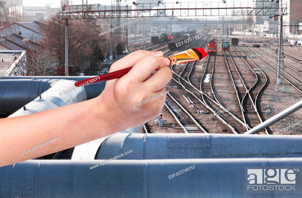Stock Photo: travel concept - hand with paintbrush paints red locomotive on railway station.