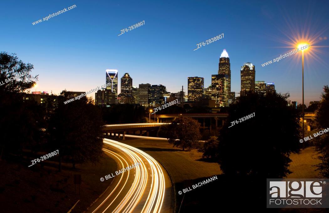 Stock Photo: Charlotte North Carolina skyline at night with traffic blurs and twilight.