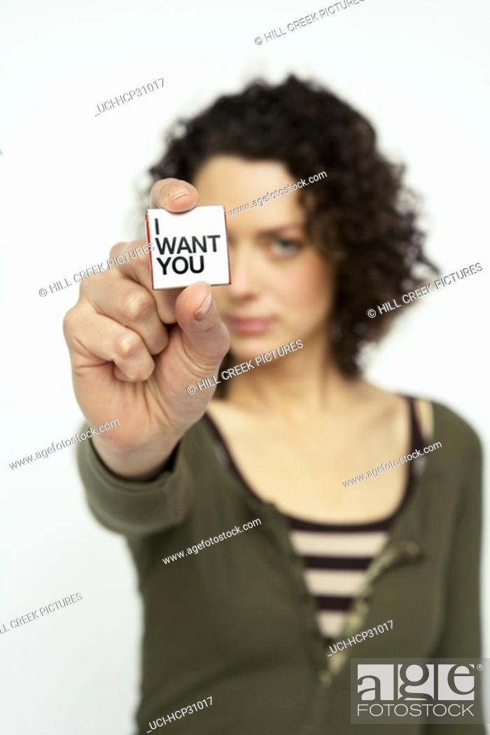 Stock Photo: Young woman holding out a square of paper saying 'I Want You'.