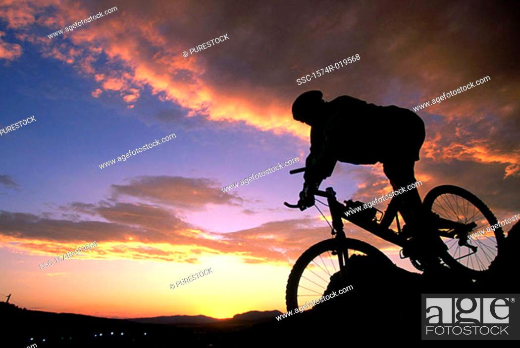 Stock Photo: Silhouette of a person mountain biking.