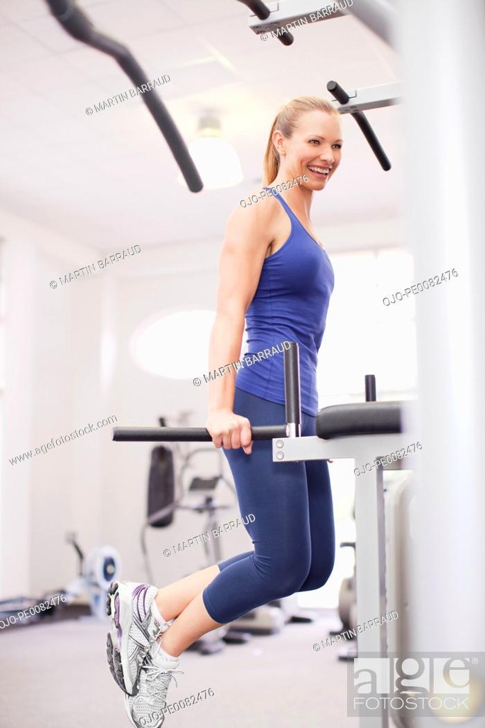 Stock Photo: Smiling woman on dip machine in gymnasium.