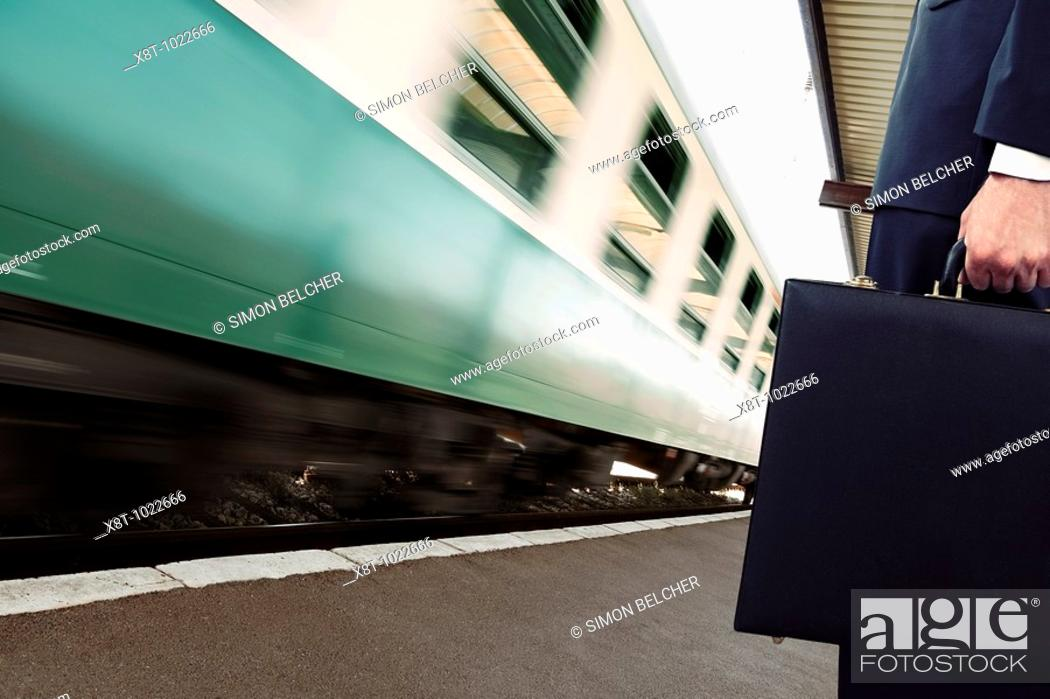 Stock Photo: Businessman Standing on a Train Station Platform as a Train Goes Past, Low Section.