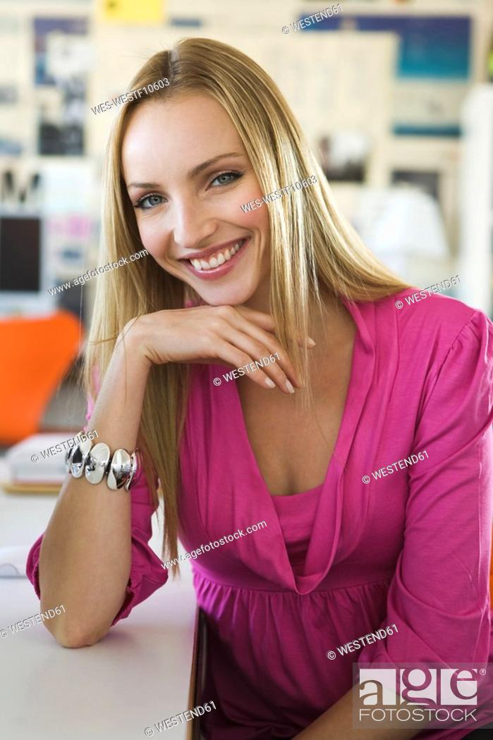 Stock Photo: Young woman in office, smiling, portrait.
