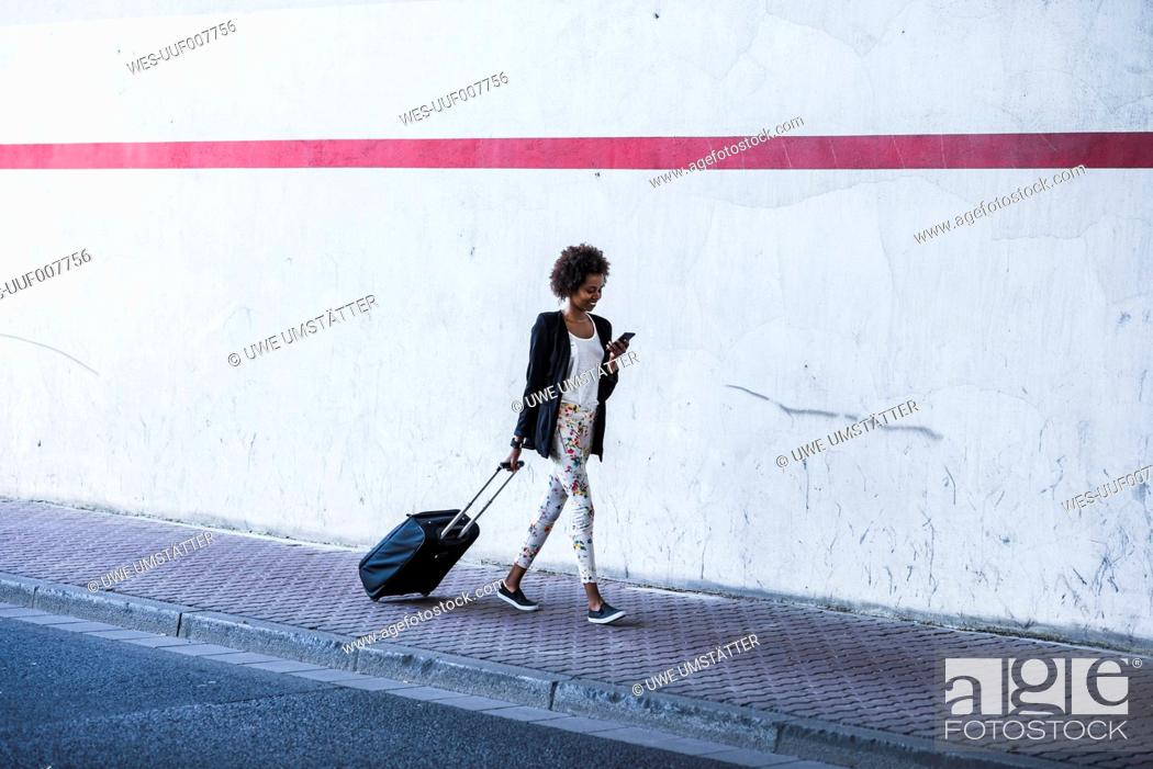 Photo de stock: Walking businesswoman with baggage looking at her smartphone.