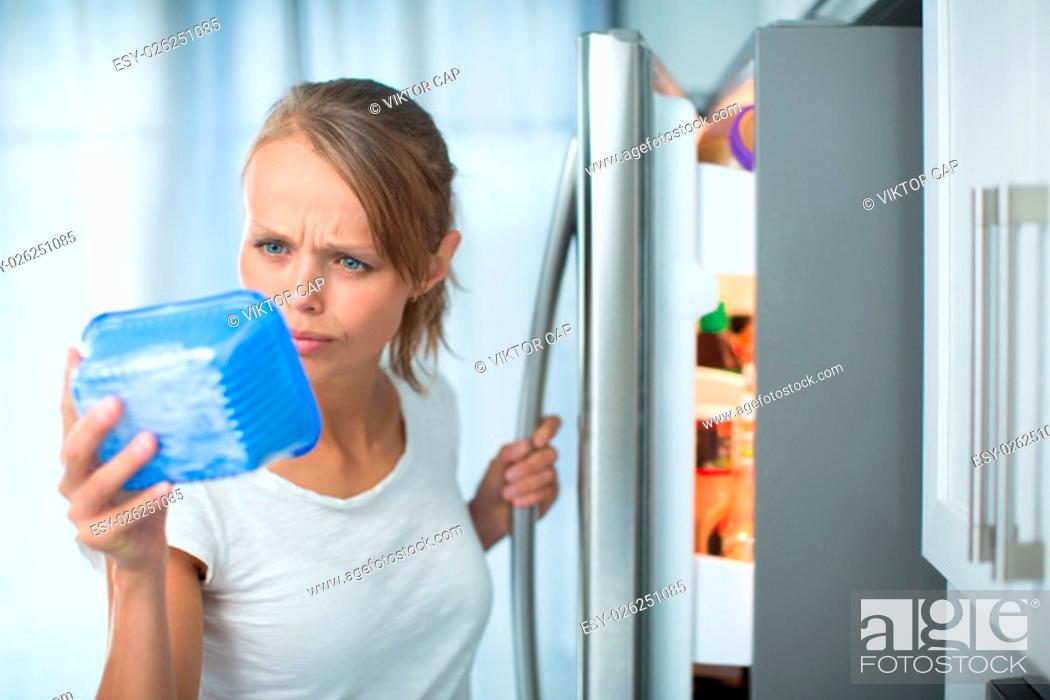 Stock Photo: Is this still fine? Pretty, young woman in her kitchen by the fridge, looking at the expiry date of a product she took from her fridge -.