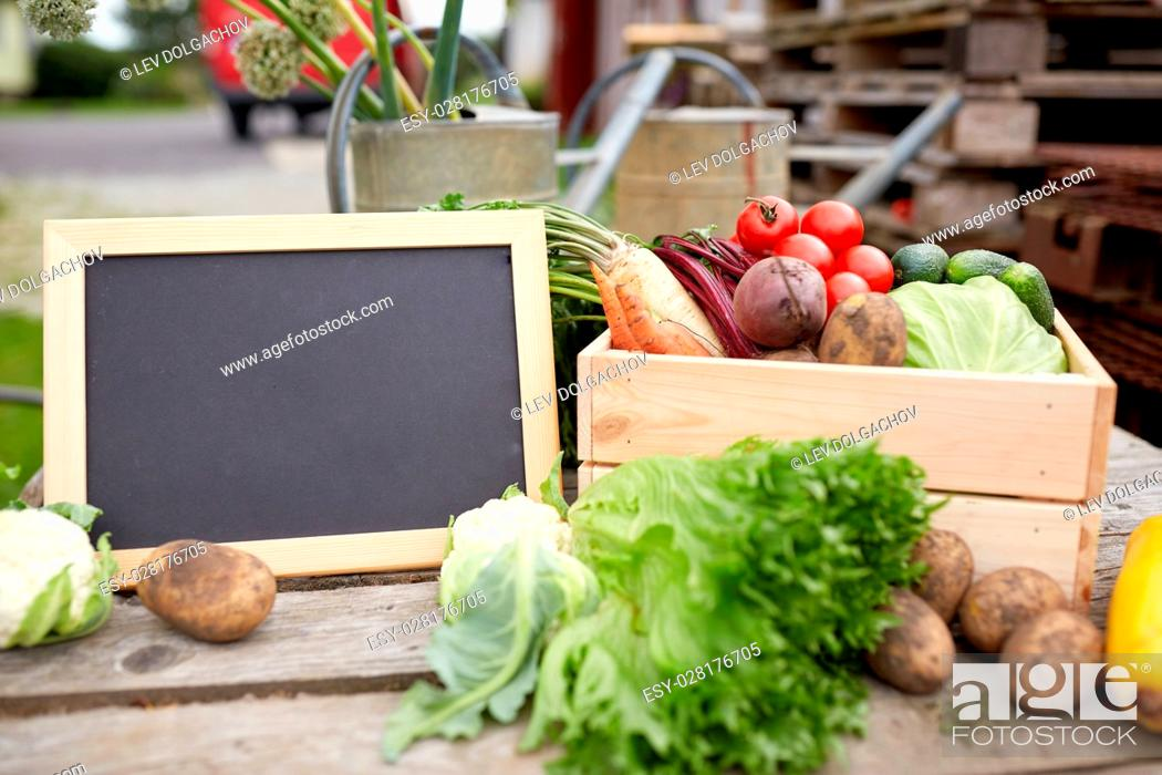 Stock Photo: harvest, food and agriculture concept - close up of vegetables with chalkboard on farm.