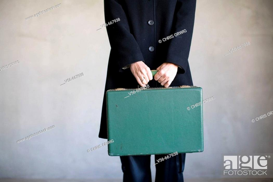 Stock Photo: A woman's torso holding an old suitcase.