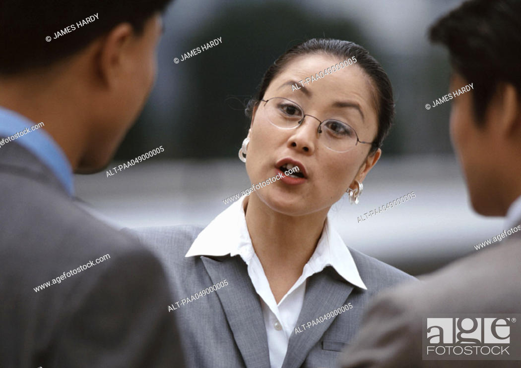 Stock Photo: Woman with open mouth, two men in foreground.