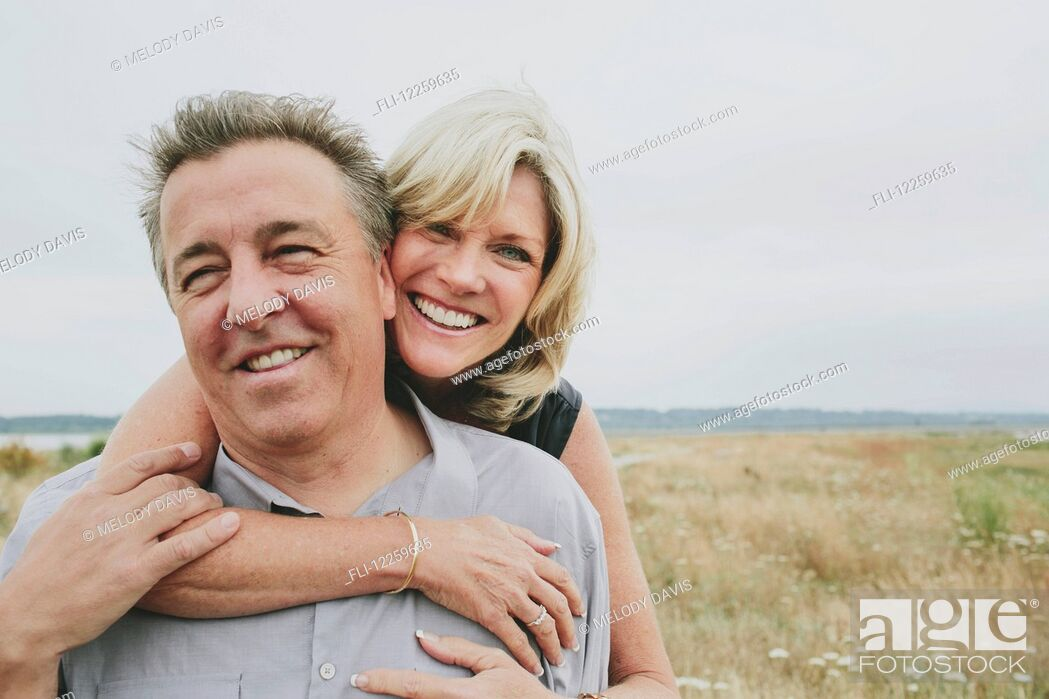 Imagen: Happy senior couple embracing on a grassy beach; Coquitlam, British Columbia, Canada.