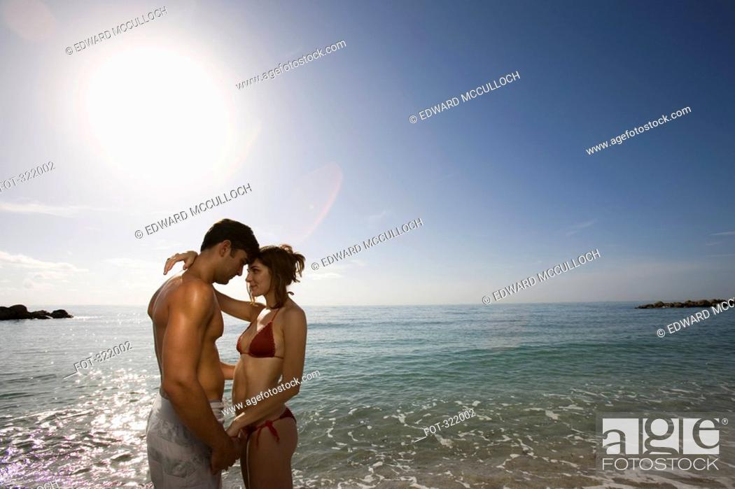 Stock Photo: Young couple embracing in front of the sea.