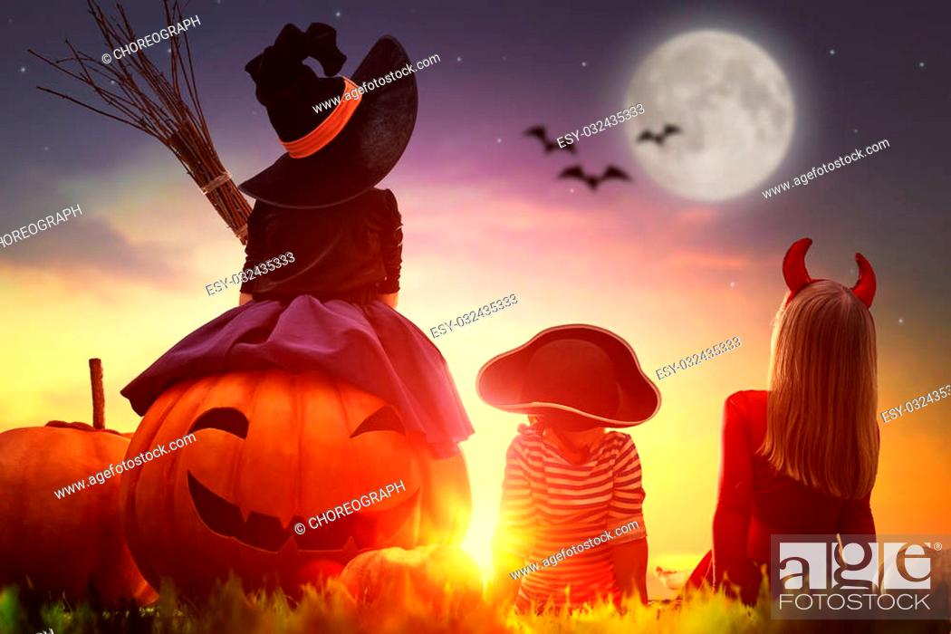 Stock Photo: Happy brother and two sisters on Halloween. Funny kids in carnival costumes outdoors. Cheerful children and pumpkins on sunset background.
