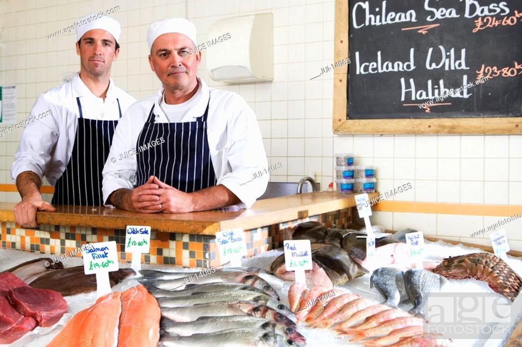 Photo de stock: Fishmongers behind counter in shop, smiling, portrait.