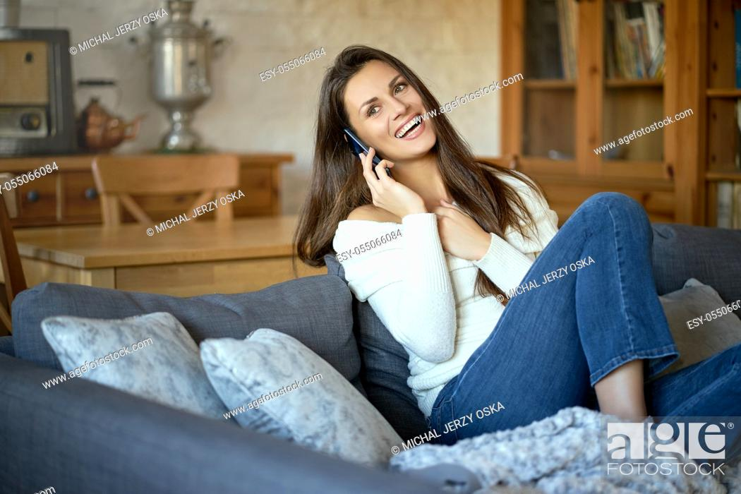 Stock Photo: beautiful young smiling woman in white sweater talking on the phone on a gray sofa.