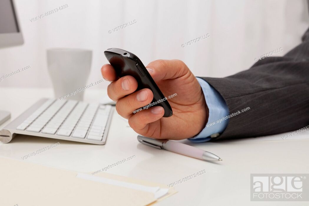 Imagen: USA, Illinois, Metamora, Man texting on his mobile in office.