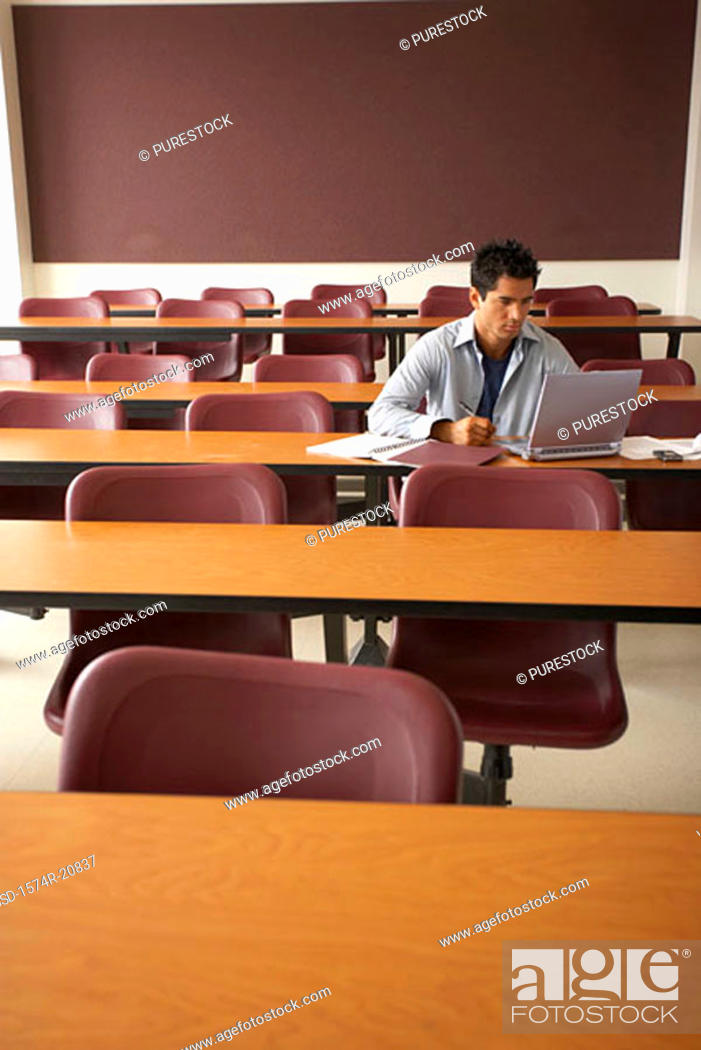 Stock Photo: College student sitting in a lecture hall and using a laptop.