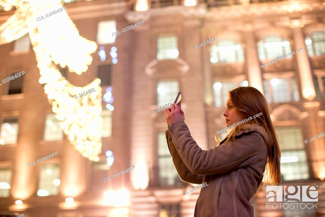Stock Photo: Young woman photographing Christmas lights, Regent Street, London, UK.