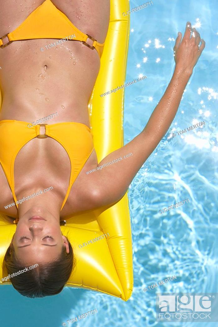 Stock Photo: Woman in bikini on flotation device in pool.
