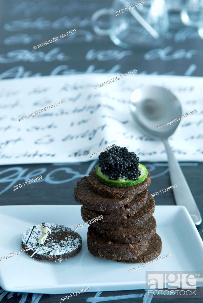 Stock Photo: A stack of pumpernickel topped with a slice of cucumber and caviar next to a model skier.
