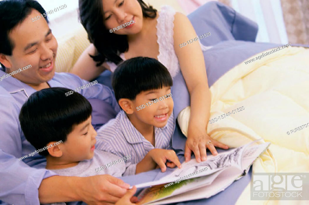 Stock Photo: Parents reading a book to their two sons.