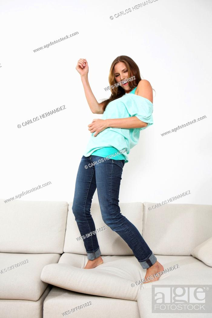 Stock Photo: Germany, Berlin, Young woman playing air guitar on couch.