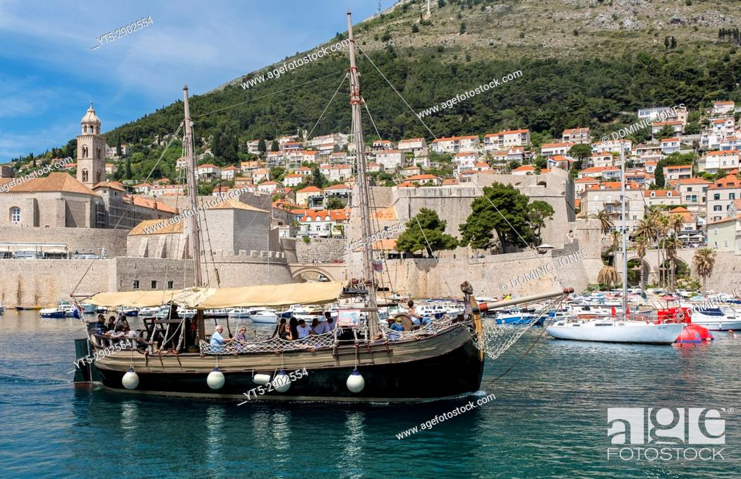 Stock Photo: A tourist cruise leaves the port of The Old City, Dubrovnik, Croatia, Europe.