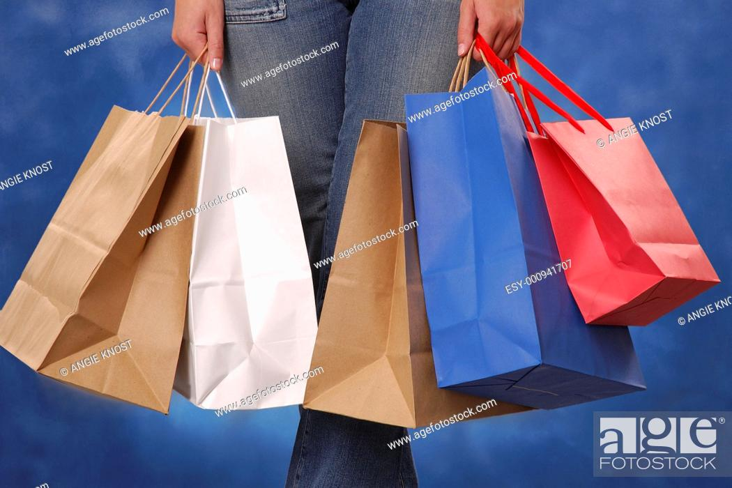 Stock Photo: Lower body view of woman holding shopping bags.