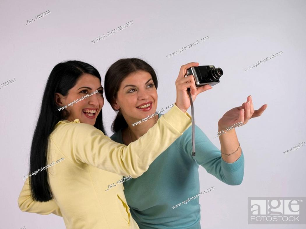 Stock Photo: Female friends taking pictures with a camera.