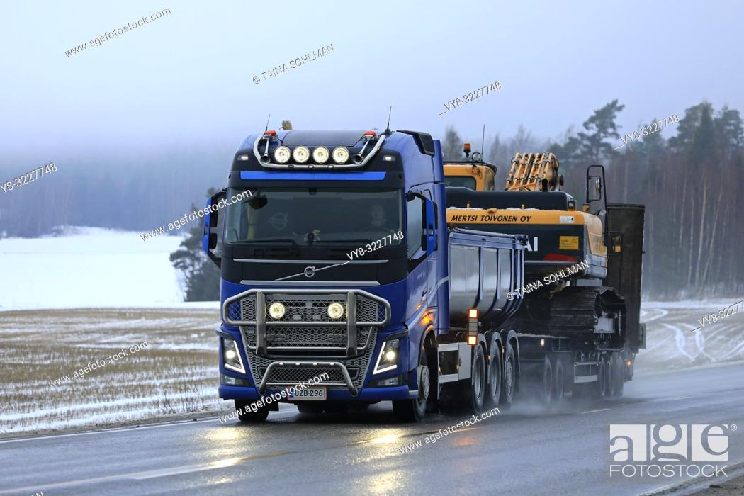 Stock Photo: Salo, Finland - January 4, 2019: Blue Volvo FH truck of M. Toivonen Oy hauls tracked excavator on trailer along wet highway on a foggy day of winter.