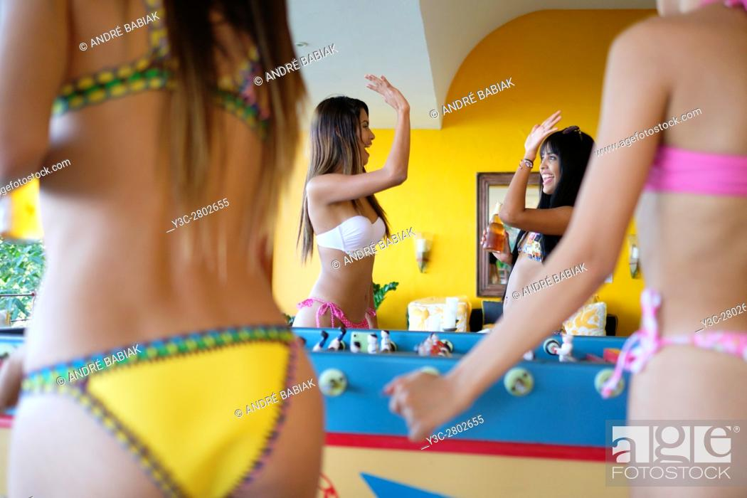 Stock Photo: Young woman high five each other after scoring at table football game.