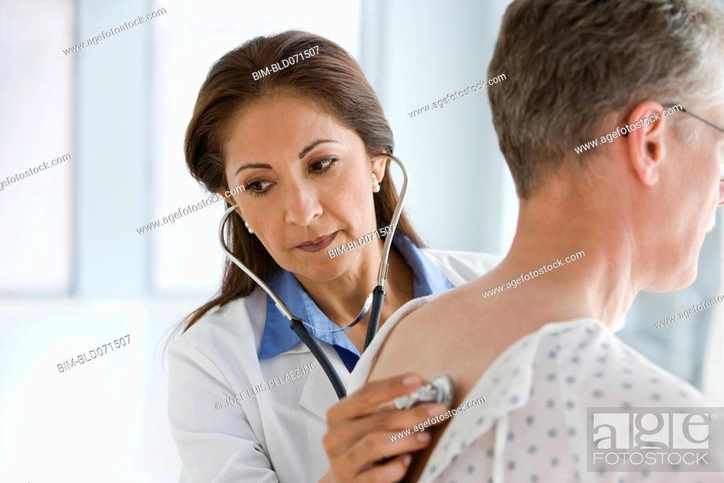 Stock Photo: Hispanic female doctor examining patient.