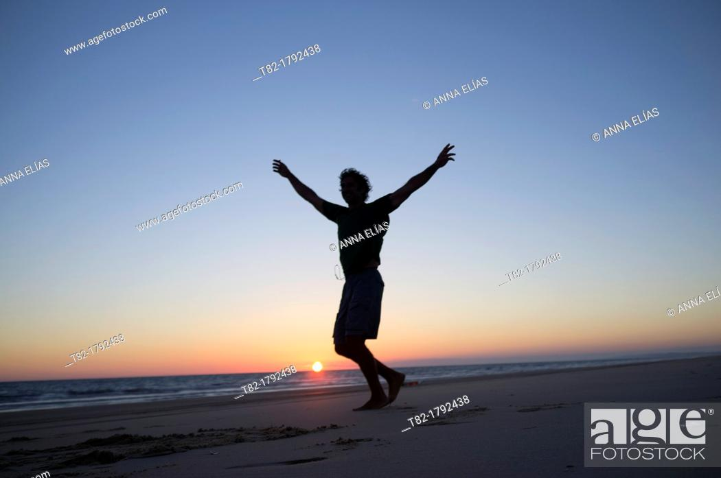 Stock Photo: silhouette man jumping on the beach at sunset, Andalusia, Spain, Europe.