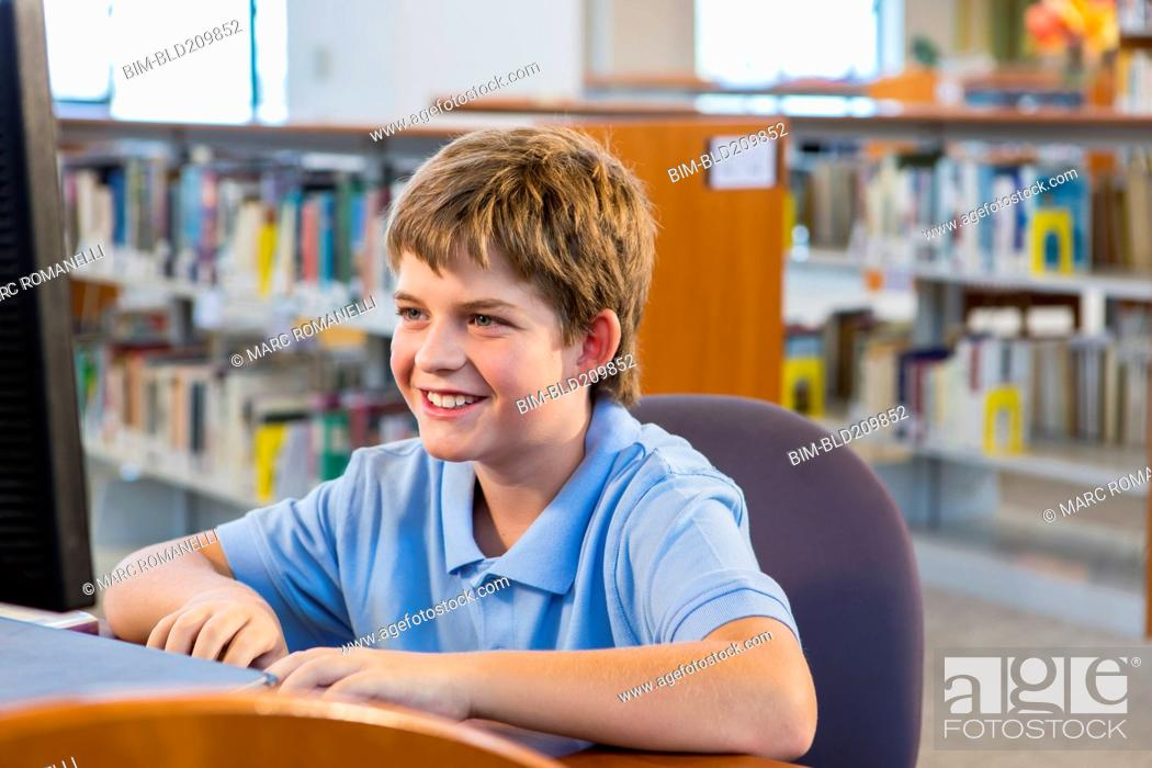 Stock Photo: Student working at computer in library.