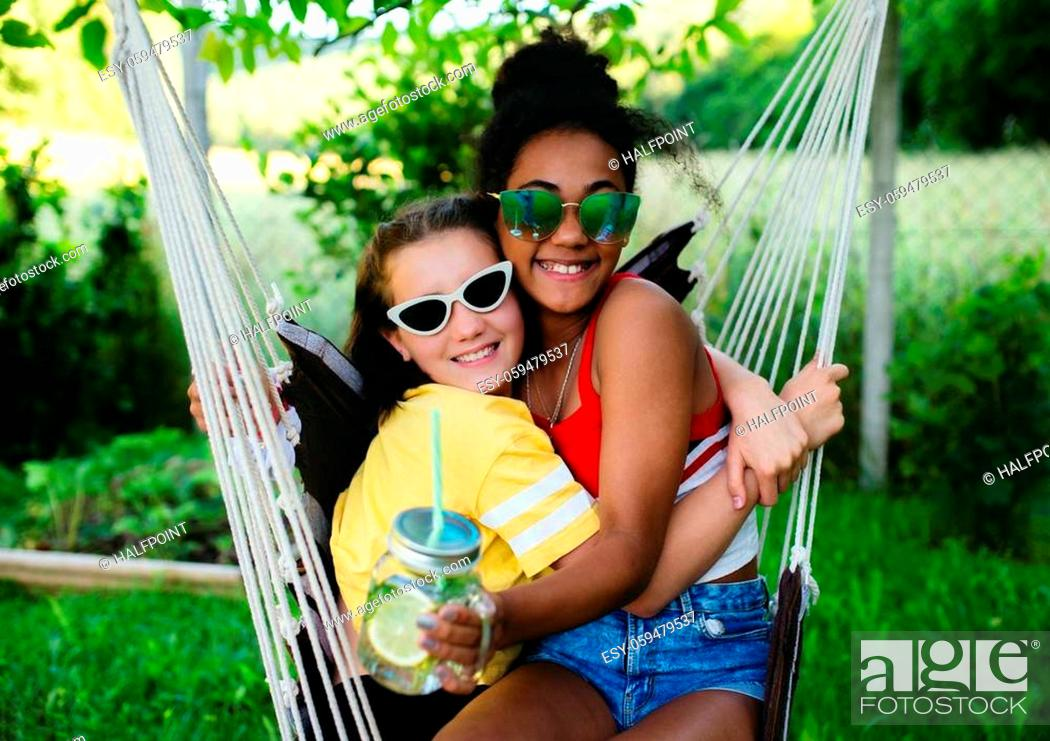 Photo de stock: Front view of cheerful young teenager girls friends outdoors in garden, hugging.