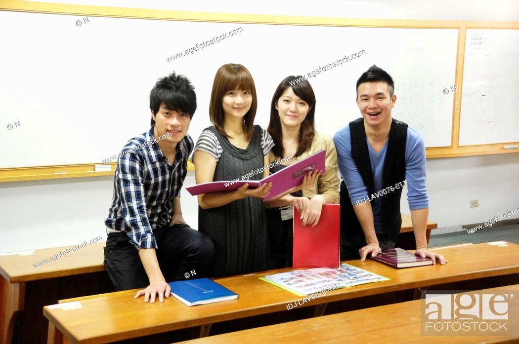 Stock Photo: University students smiling in a classroom.