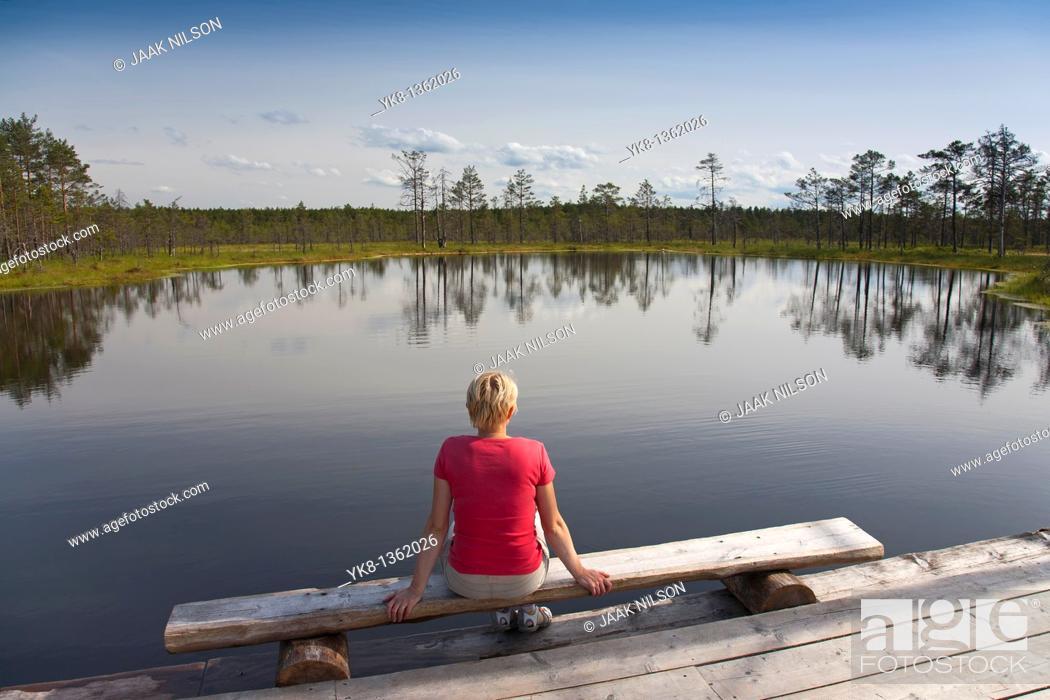 Stock Photo: Young Woman Sitting by Bog Lake in Viru Bog, Lääne-Viru County, Estonia, Europe.