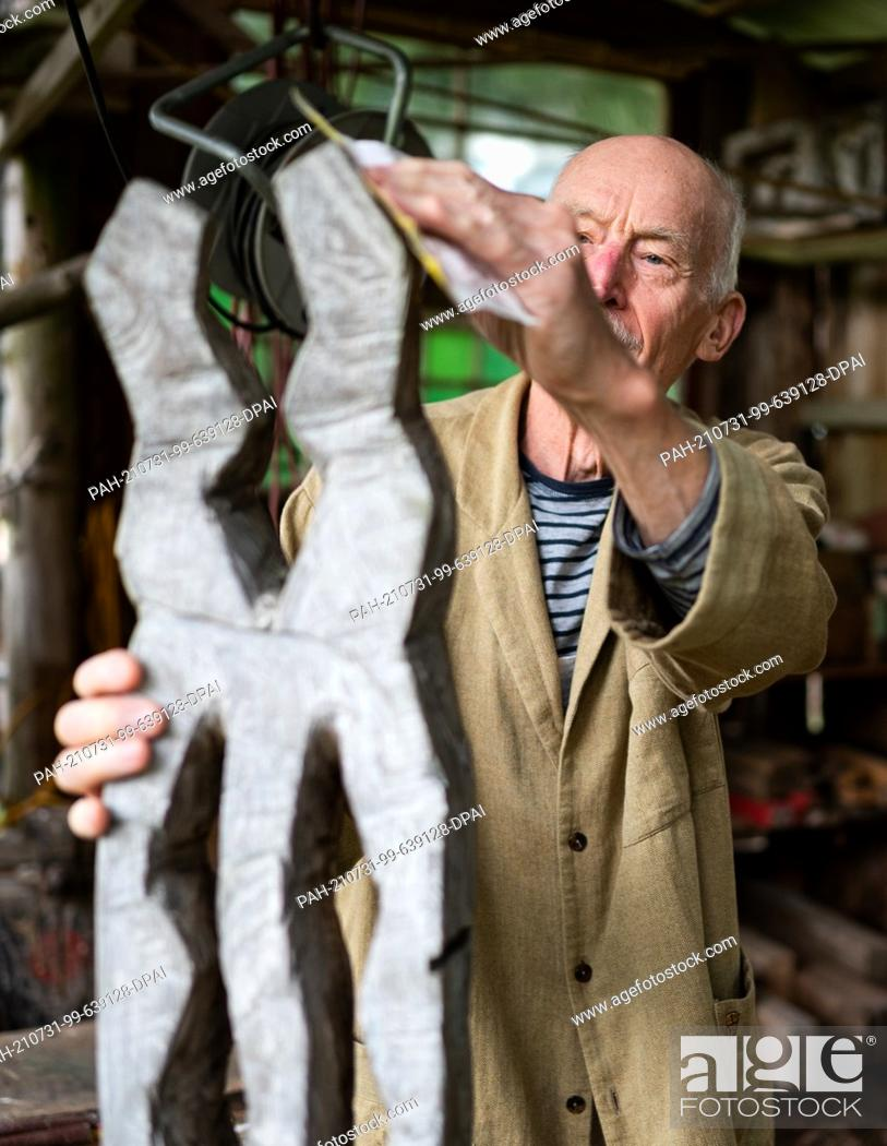 """Stock Photo: 31 July 2021, Lower Saxony, Kiefen: Udo Schr·der, sculptor, puts the finishing touches to a sculpture as part of the """"""""Kulturelle Landpartie""""""""."""