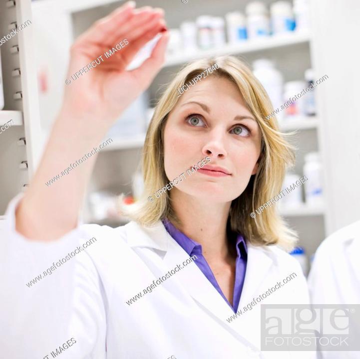 Stock Photo: Pharmacists examining pill and pill bottle.