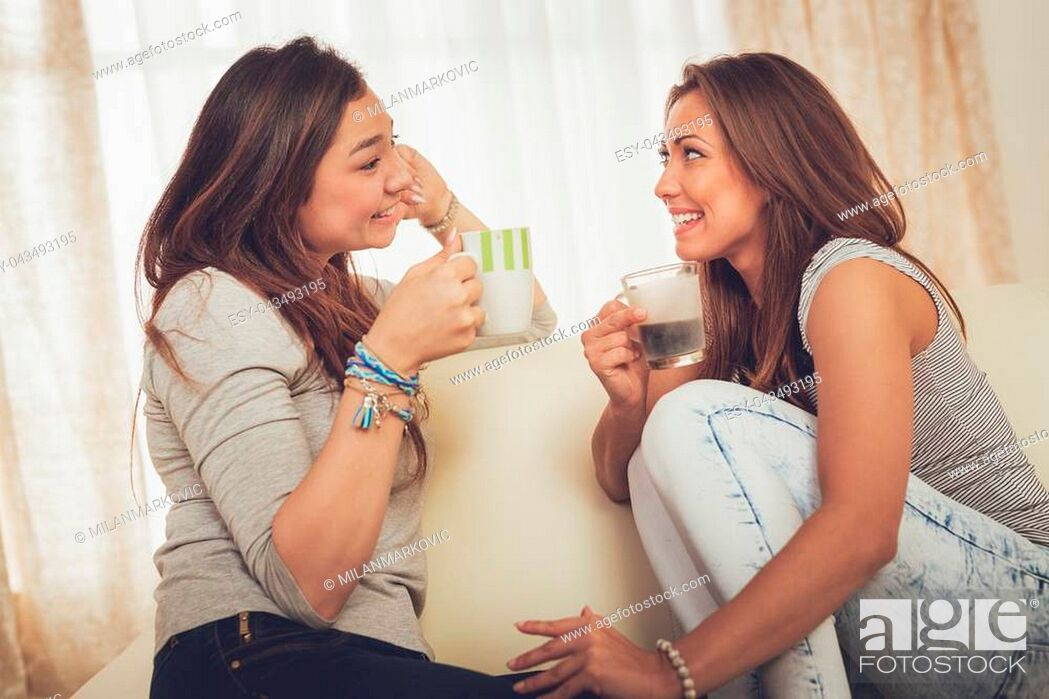 Stock Photo: Two young cheerful female friends enjoying coffee and talking in an apartment.