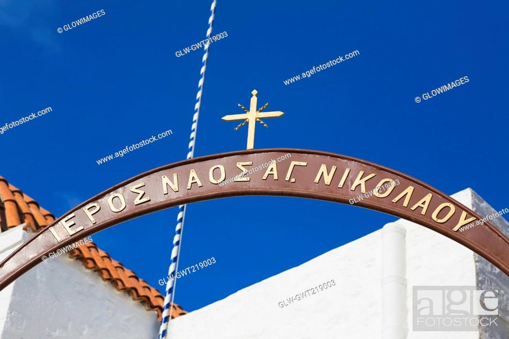 Stock Photo: Low angle view of a cross over an arch, Patmos, Dodecanese Islands, Greece.