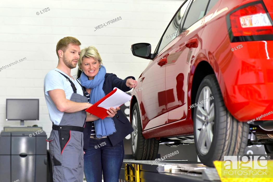 Photo de stock: Car mechanic with client in workshop at car.