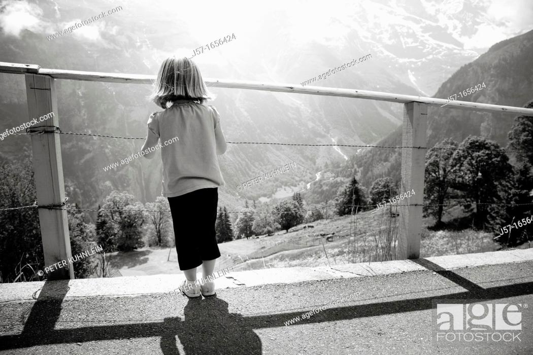 Stock Photo: Young girl looking through a fence at a mountain scene in Mürren, Switzerland.