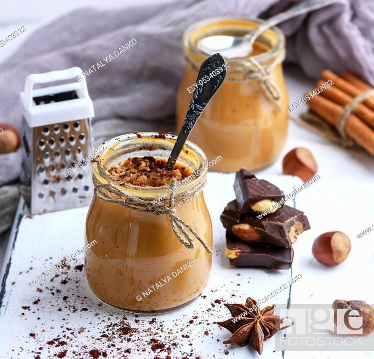 Stock Photo: Caramel dessert Toffee in a glass jar on a white texture table, close up.