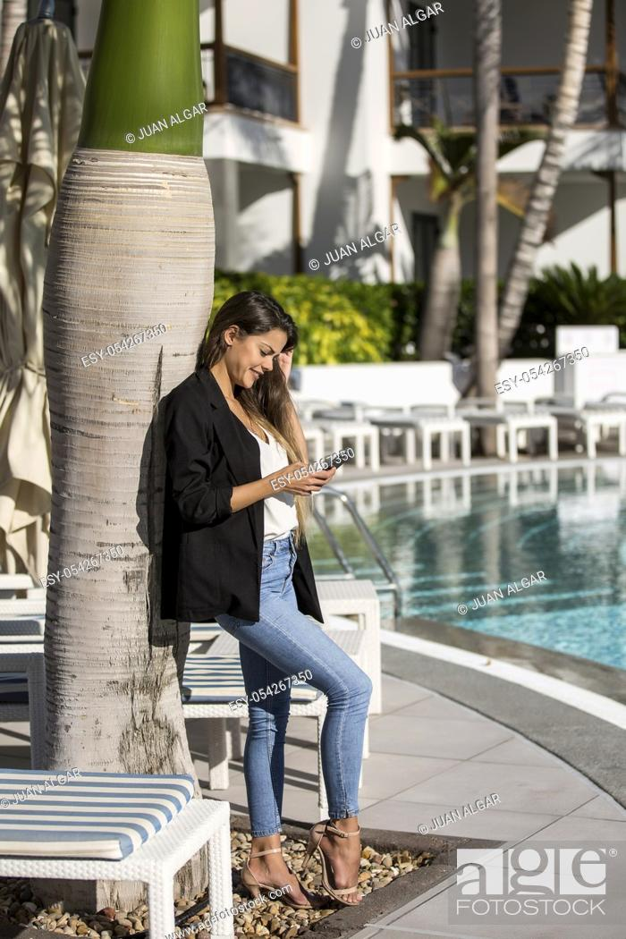 Stock Photo: Trendy young brunette using smartphone and leaning on palm tree while relaxing in poolside.