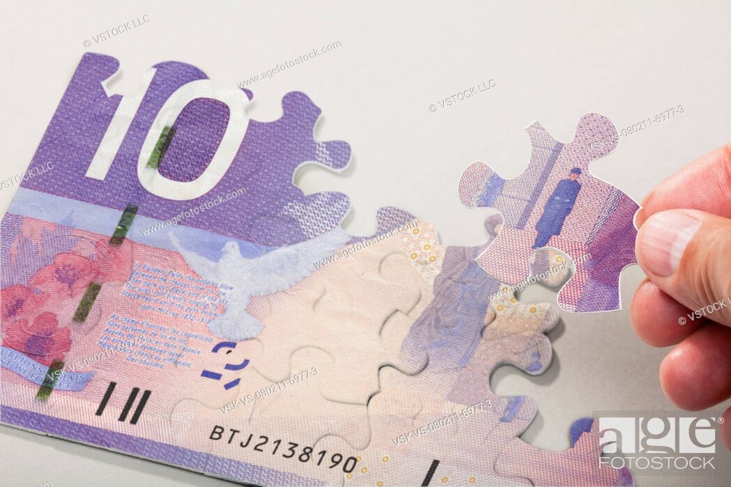 Stock Photo: Male hand arranging puzzle pieces creating canadian currency.